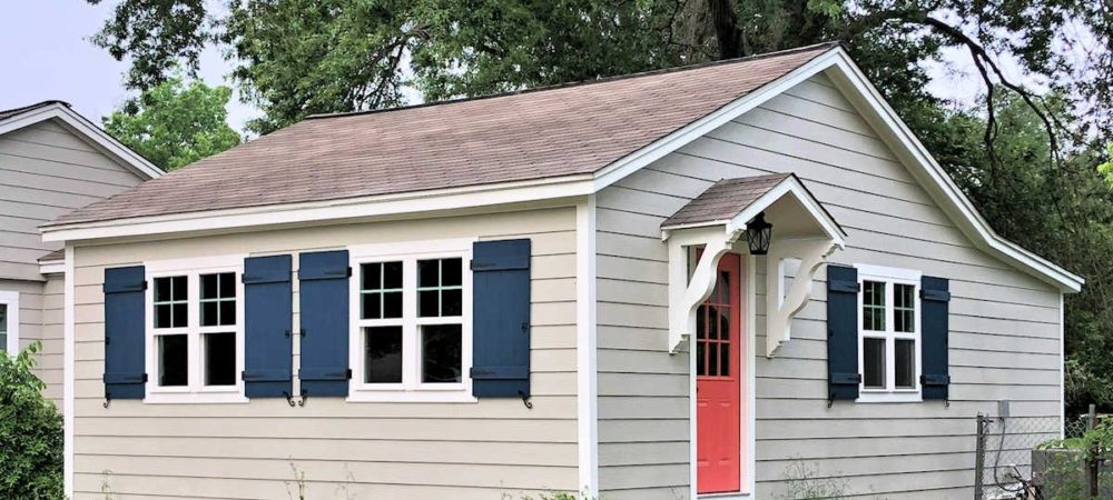 navy-blue-DIY-board-and-batten-shutters-with-black-hinges-pulls-and-shutters-dogs